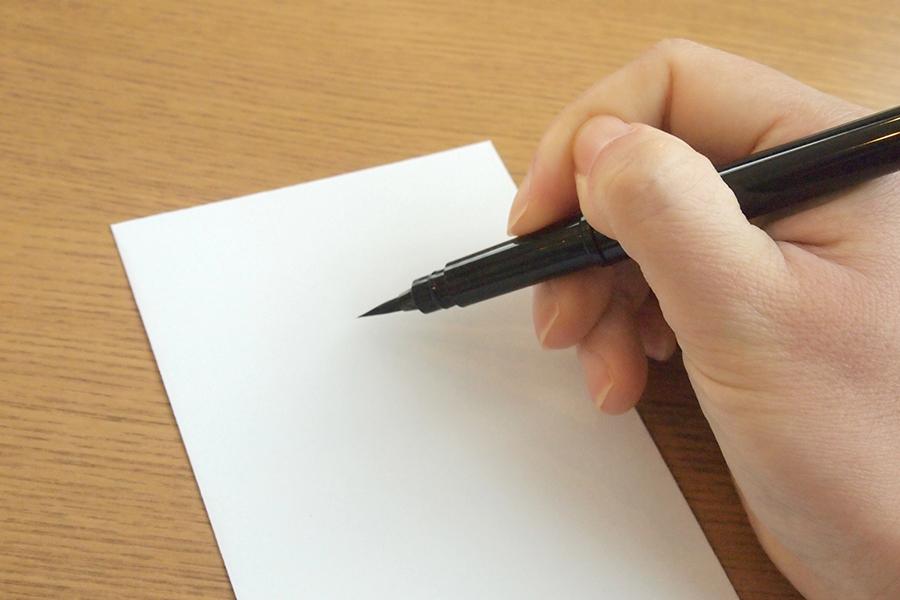 筆ペンで字を書くイメージ写真