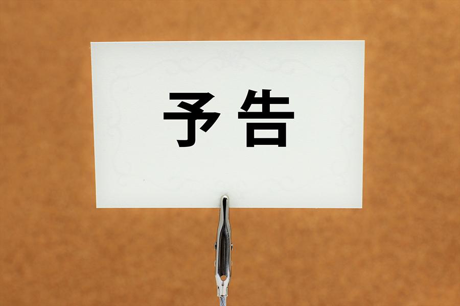 「予告」の文字が書かれているクリップに挟まれた紙の写真