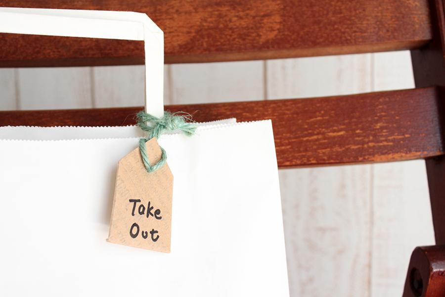 紙袋に「Take Out」と書かれたタグが付けられたテイクアウトのイメージ写真