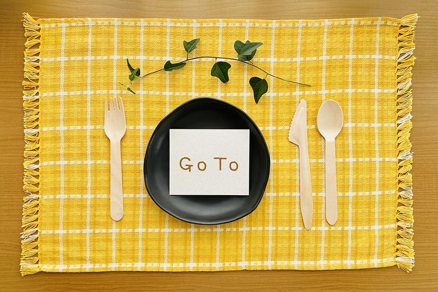 スプーン・フォーク・ナイフのセットと「Go To」と書かれた紙が置いてあるお皿