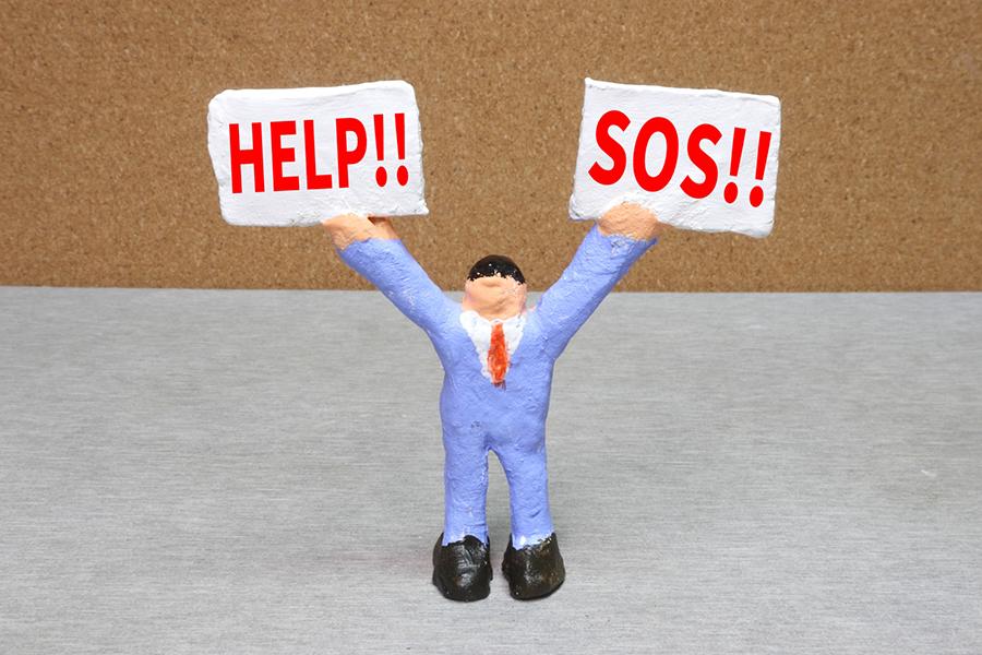 人形が掲げている札に書かれた「HELP!!」と「SOS!!」の文字